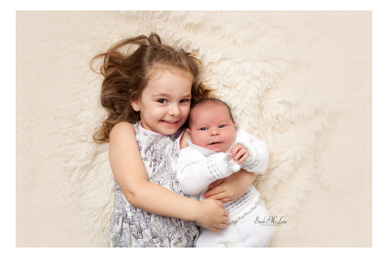 newborn baby with older sister laying down  Baby and family photo's clitheroe, lancashire by Sarah Mclean