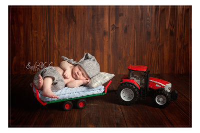 newborn baby photo on a tractor by Sarah Mclean photography in clitheroe lancashire